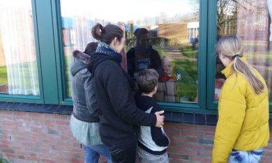 gezin communiceert via het raam met opa in een verzorgingstehuis