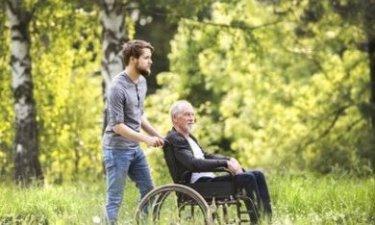 zoon wandelt samen met zijn invalide vader