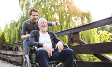 jongere met opa in rolstoel