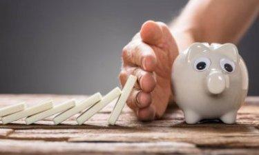 dominostenen die omvallen richting spaarpot worden gestopt door een hand