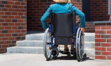 vrouw in rolstoel wacht voor hulp om de trap op te gaan