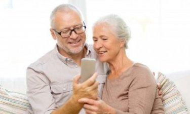 Senior man en vrouw kijken naar mobieltje