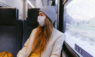 vrouw met mondkapje in trein