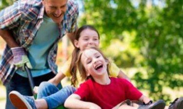 man met kinderen in kruiwagen