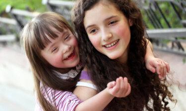 blije zusjes, waarvan 1 zusje Downs syndroom heeft, knuffelen